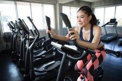 mujer joven asiática de la aptitud en ropa de deportes que ejercita con biking en club del gimnasio del deporte entrenamiento de  imagenes de archivo
