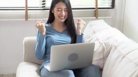 Mujer joven asiática del retrato hermoso que trabaja el ordenador portátil en línea con sonrisa y la sentada feliz en el sofá en
