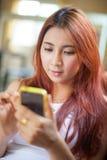 Mujer joven asiática feliz que miente usando el teléfono elegante Imagen de archivo libre de regalías