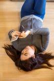 Mujer joven asiática feliz que miente usando el teléfono elegante Fotos de archivo