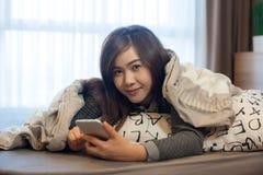 Mujer joven asiática feliz que miente usando el teléfono elegante Fotografía de archivo libre de regalías