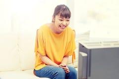 Mujer joven asiática feliz que ve la TV en casa Fotografía de archivo