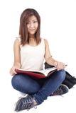 Mujer joven asiática hermosa con la mochila que lee el libro rojo Fotos de archivo libres de regalías