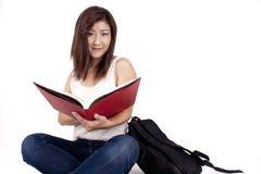 Mujer joven asiática hermosa con la mochila que lee el libro rojo Imágenes de archivo libres de regalías
