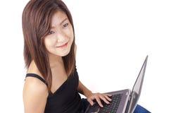 Mujer joven asiática hermosa que mecanografía en el ordenador portátil Fotos de archivo
