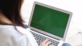 Mujer joven asiática hermosa que miente en cama usando la pantalla del verde de la exhibición del ordenador portátil en el dormit