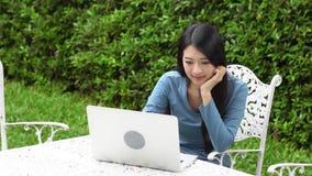 Mujer joven asiática hermosa que trabaja el ordenador portátil en línea con sonrisa y la sentada feliz en silla en el jardín