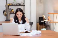 Mujer joven asiática hermosa que trabaja en línea en el ordenador portátil que se sienta en la cafetería fotos de archivo libres de regalías