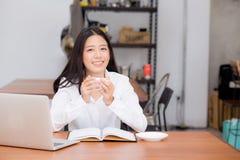 Mujer joven asiática hermosa que trabaja en línea en el ordenador portátil y el café de la bebida que se sientan en la cafetería imagen de archivo libre de regalías