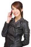 Mujer joven asiática que llama por el teléfono Imagen de archivo libre de regalías