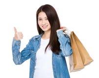 Mujer joven asiática que muestra el pulgar para arriba con el panier Imagen de archivo libre de regalías