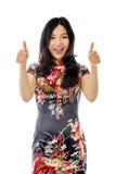 Mujer joven asiática que muestra los pulgares para arriba de ambas manos aisladas en el fondo blanco fotografía de archivo