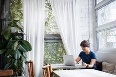 Mujer joven asiática que sostiene la tarjeta de crédito y que usa el ordenador portátil fotografía de archivo