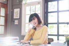 Mujer joven asiática que usa smartphone en casa Foto de archivo libre de regalías