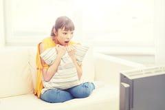 Mujer joven asiática que ve la TV en casa Fotos de archivo libres de regalías
