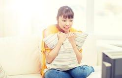 Mujer joven asiática que ve la TV en casa Imágenes de archivo libres de regalías