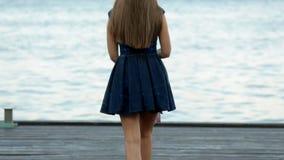 Mujer joven asombrosa en un vestido corto y tacones altos azules que camina en el embarcadero de madera por el mar almacen de video