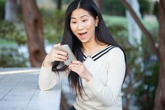 Mujer joven asombrosa que mira feliz en su pantalla del teléfono móvil Imagen de archivo