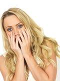 Mujer joven asustada chocada y asustada que oculta detrás de sus manos Imagen de archivo libre de regalías