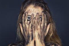 Mujer joven asustada con la cara y los brazos sucios Foto de archivo libre de regalías