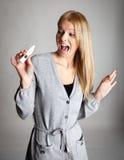 Mujer joven asustada de resultados de la prueba de embarazo Foto de archivo