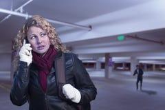 Mujer joven asustada en el teléfono celular en estructura del estacionamiento Imagenes de archivo