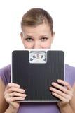 Mujer joven asustada que mira detrás de una escala del peso Imagen de archivo