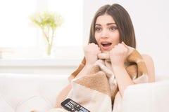 Mujer joven asustada que ve la TV Fotografía de archivo