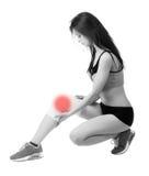 Mujer joven atlética con el vendaje elástico en su pierna Aislado Foto de archivo