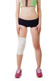 Mujer joven atlética con el vendaje elástico en su pierna Aislado Foto de archivo libre de regalías