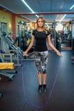 Mujer joven atlética en ropa de deportes que ejercita con la cuerda que salta Imagenes de archivo