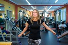 Mujer joven atlética en ropa de deportes que ejercita con la cuerda que salta Foto de archivo