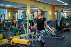 Mujer joven atlética en ropa de deportes que ejercita con la cuerda que salta Imágenes de archivo libres de regalías