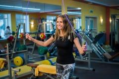 Mujer joven atlética en ropa de deportes que ejercita con la cuerda que salta Imagen de archivo libre de regalías