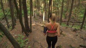Mujer joven atlética que corre abajo de Forest Trail And Going Down de la colina almacen de metraje de vídeo