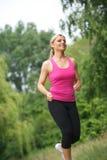 Mujer joven atlética que corre al aire libre Imagen de archivo