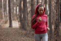 Mujer joven atlética que corre en la naturaleza Fotos de archivo