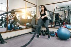 Mujer joven atlética que ejercita en el gimnasio usando cuerdas de la batalla Aptitud, deporte, entrenamiento, gente, concepto sa foto de archivo