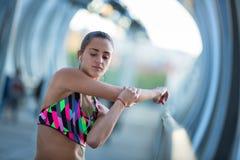 Mujer joven atlética que estira antes de ejercicio mientras que escucha la música Fotografía de archivo