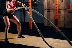 Mujer joven atlética que hace algunos ejercicios aptos de la cruz con la cuerda al aire libre imagenes de archivo