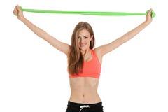 Mujer joven atlética que hace entrenamiento con la cinta fisia del látex de la cinta foto de archivo