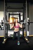 Mujer joven atlética que hace estocadas con la máquina del forjador fotos de archivo