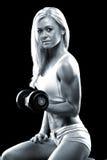 Mujer joven atlética que hace un entrenamiento de la aptitud con pesa de gimnasia foto de archivo