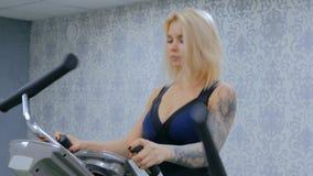 Mujer joven atlética que se resuelve en la máquina de pasos en el gimnasio almacen de metraje de vídeo