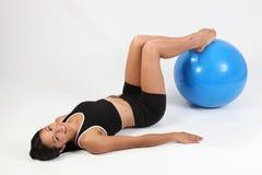 Mujer joven atlética feliz que usa la bola del ejercicio Imagenes de archivo