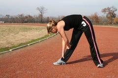 Mujer joven atlética que estira en la pista Imagen de archivo