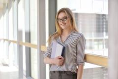 Mujer joven atractiva alegre con la mochila y los cuadernos que se colocan y que sonríen en la universidad, collage Blonde joven Imagenes de archivo
