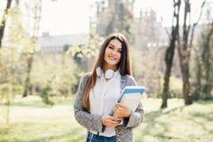 Mujer joven atractiva alegre con los cuadernos que se colocan y que sonríen en parque Fotos de archivo