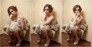 Mujer joven atractiva atractiva envuelta en un abrigo de pieles que se sienta en el piso en la habitación El estar femenino del p Fotografía de archivo libre de regalías