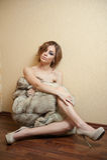 Mujer joven atractiva atractiva envuelta en un abrigo de pieles que se sienta en el piso en la habitación El estar femenino del p Imagenes de archivo